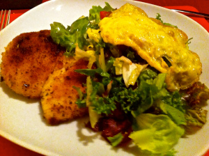 milanese cutlet served with salad and omelette