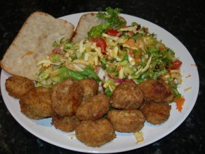 salad is served with bread and chicken balls