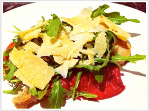 bresaola served on bread with parmesan and cheese