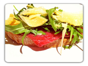 bresaola served with slices of parmesan and rocket