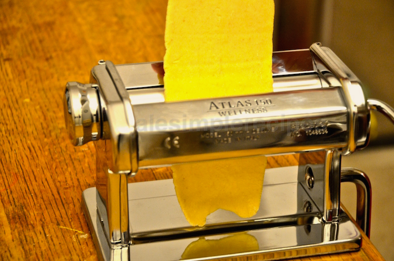 Pass each sausage of dough through a hand-cranked pasta roller